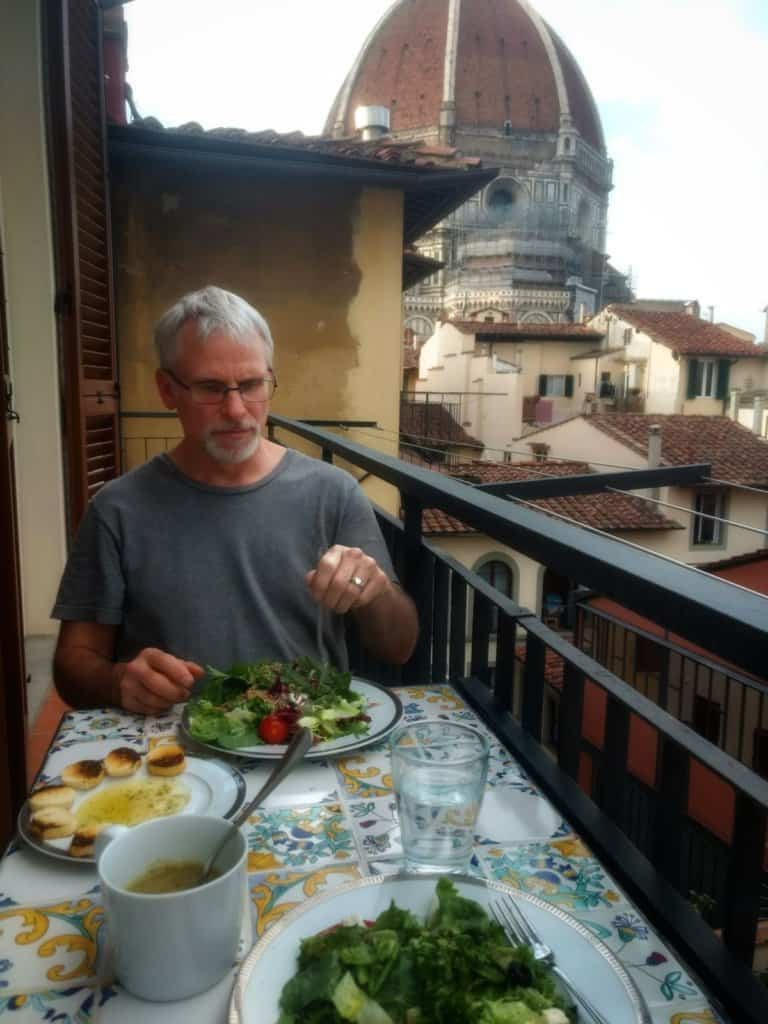 Man with grey hair eating a salad on a small balcony with the Florence Duomo dome in the background.