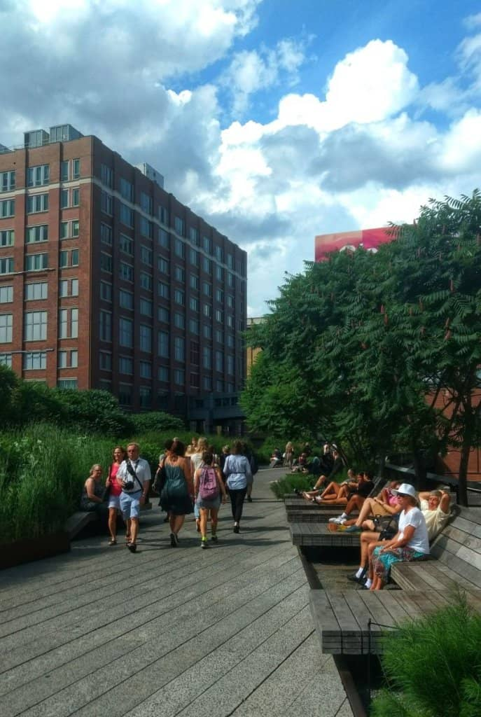 People walking on the New York City High Line with buildings and trees in the background.
