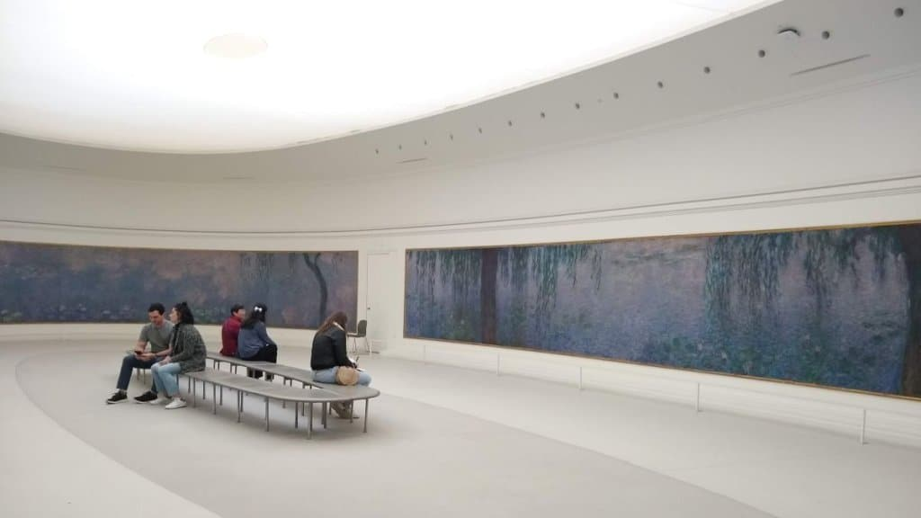 Monet's Water Lilies at Musee de l'Orangerie with just a few people seated in the room.