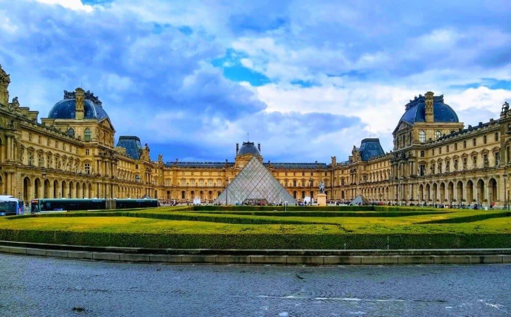 The Louvre pyramid in front of the Louvre palace with a blue sky.