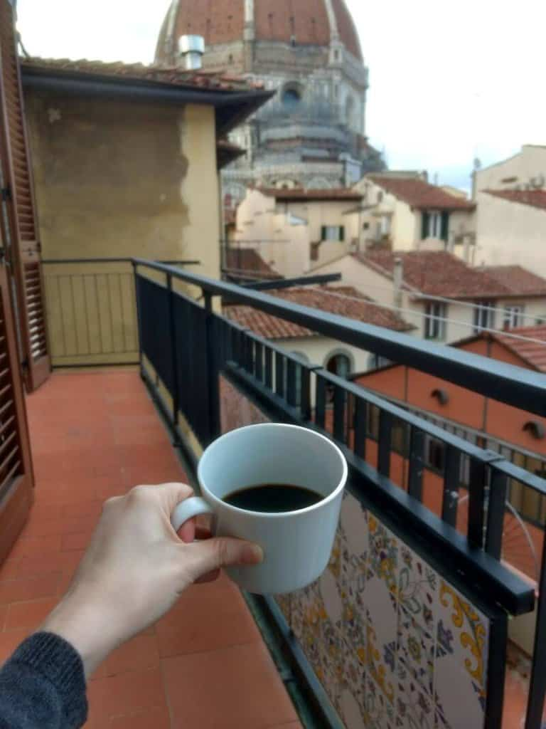 Cup of coffee on a balcony in Florence, Italy, with the Duomo dome in the distance.