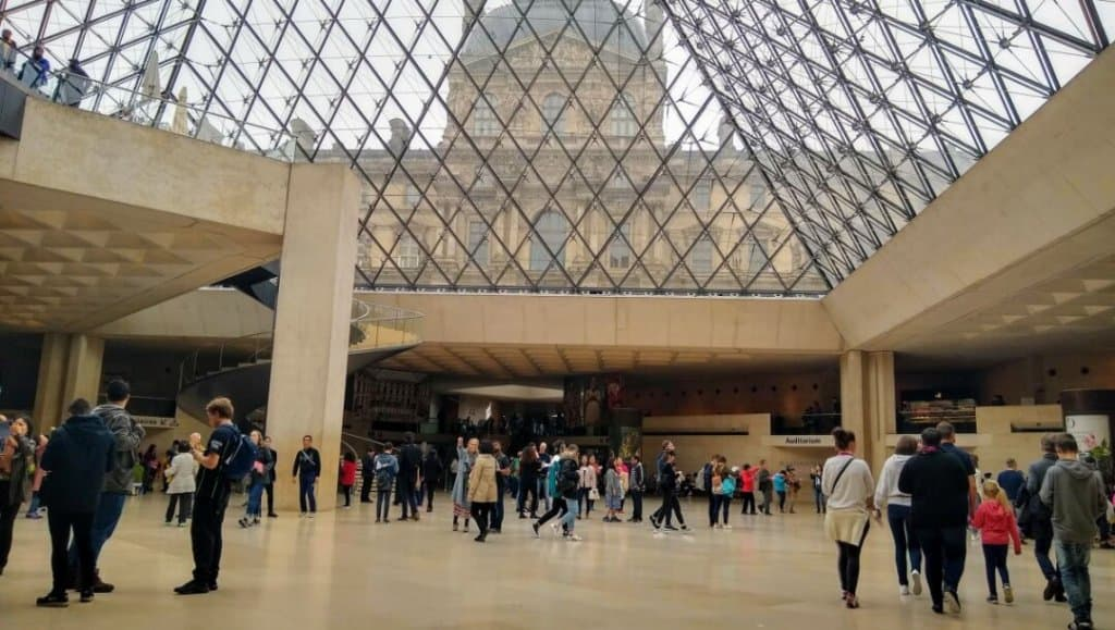 View of the underside of the Louvre pyramid with many museum guests walking around.