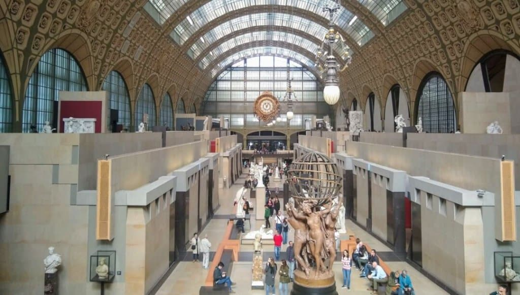 Central sculpture gallery of Musee d'Orsay from the mezzanine with the clock on the wall in the background.