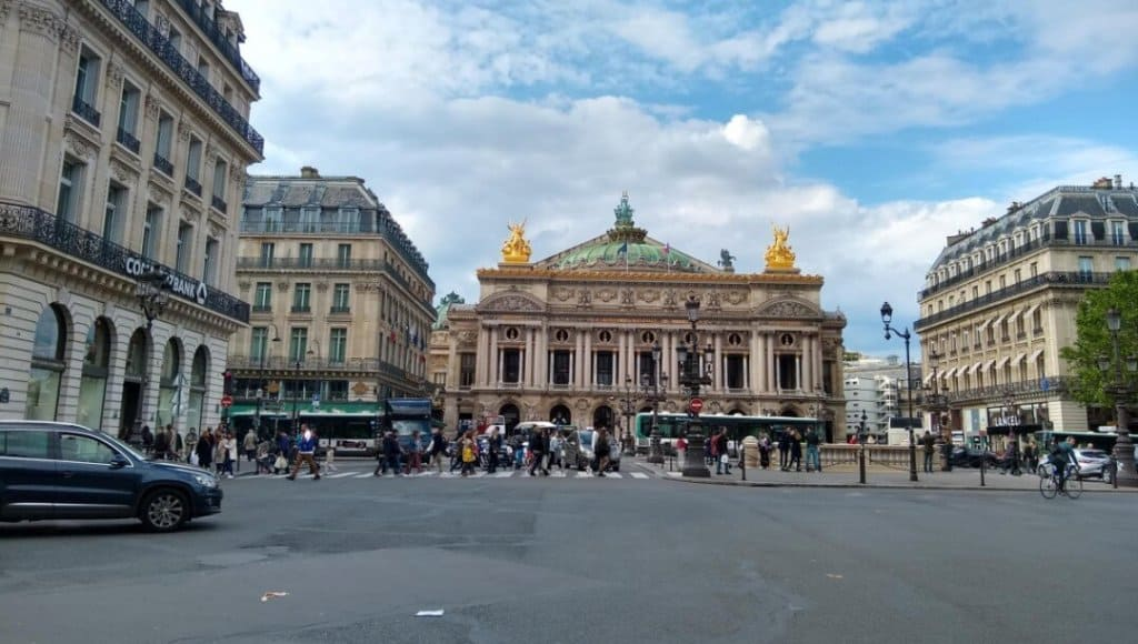 View of the Palais Garnier (Paris Opera House) from across the street with vehicles and pedestrians crossing the street.