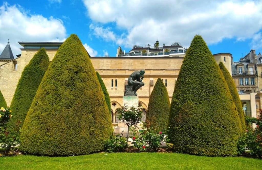 Rodin's Thinker sculpture in the middle of trimmed hedges in the artist's garden in Paris.