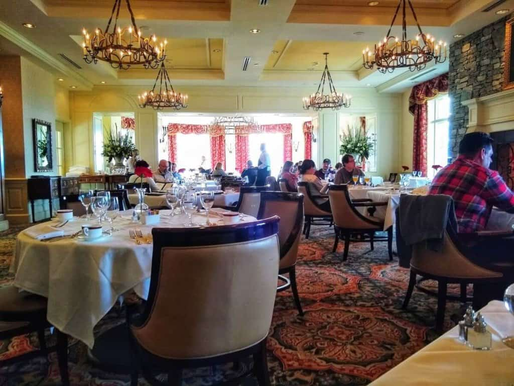 Luxurious dining room with large windows and lit chandeliers.