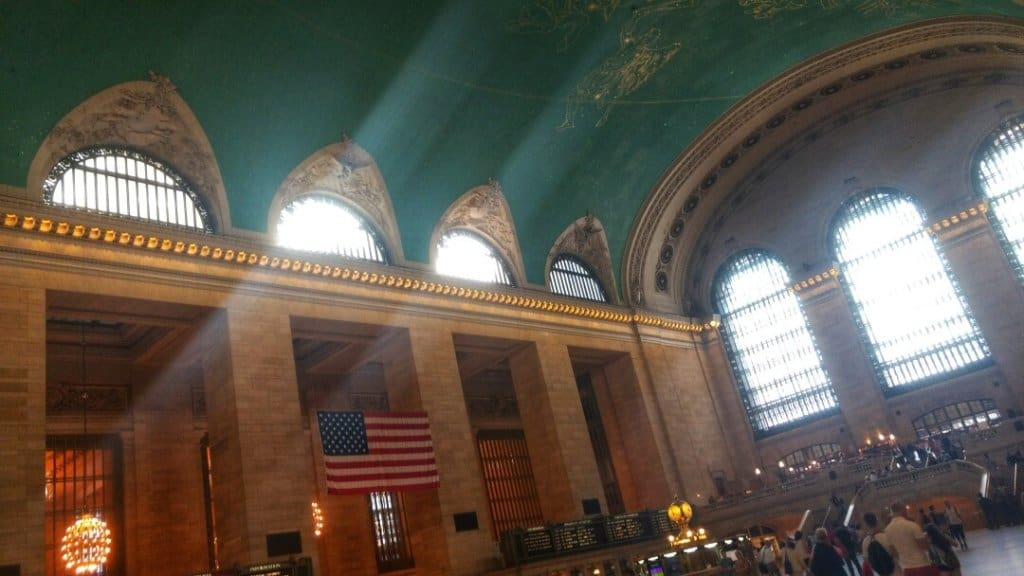 Inside the Grand Central Terminal main hall with sun streaming in through the large windows.