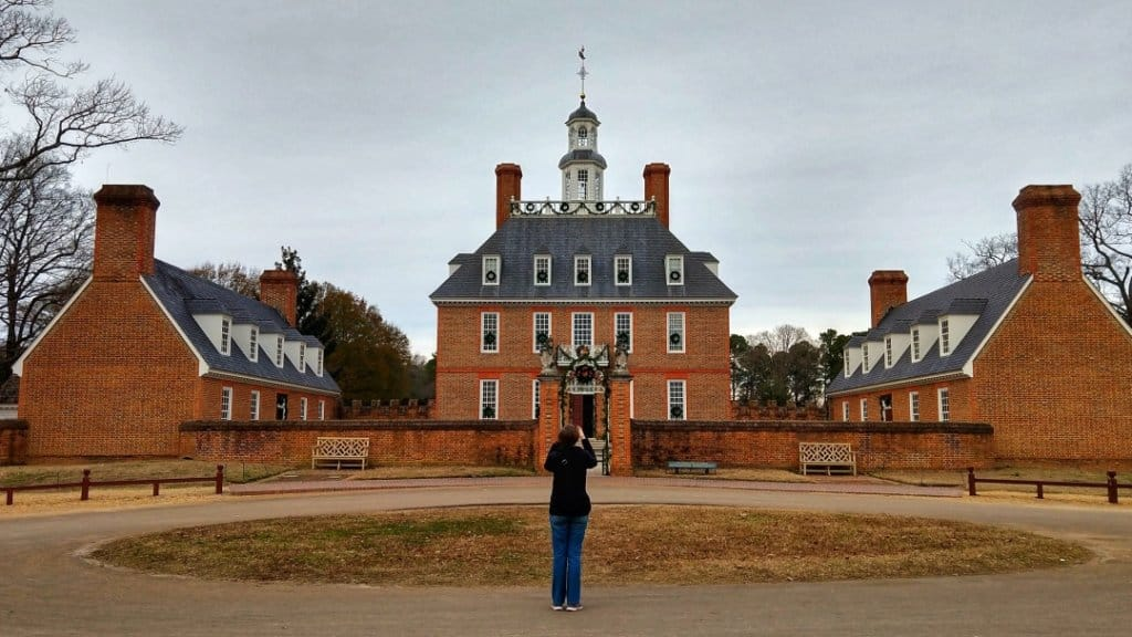 Women standing in front of the governor's palace in Colonial Williamsburg and taking a photo with her phone.