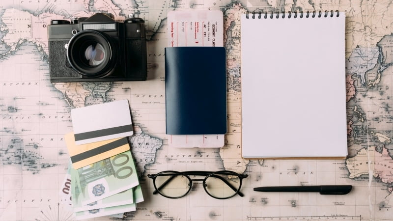 World map with several items laying on it like cash, a notebook, a passport and a camera.