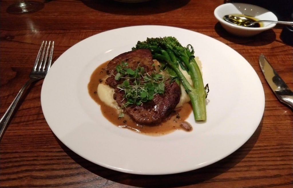 Steak and broccolini on a white plate at The Bistro at Biltmore Estate Winery