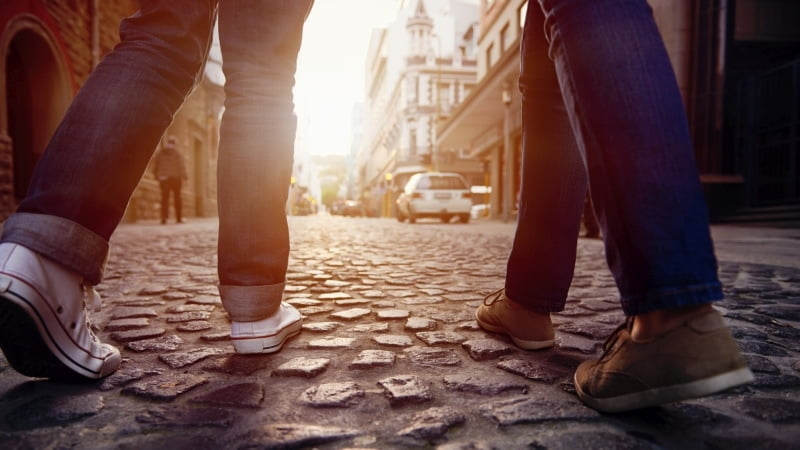 Couple wearing jeans and casual shoes walking on a cobblestone street
