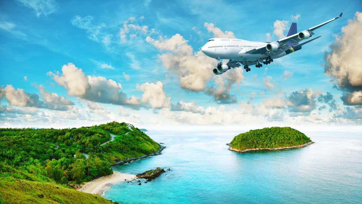 Airplane flying over islands with clear blue water